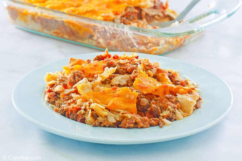 taco casserole on a light blue plate and in a glass baking dish