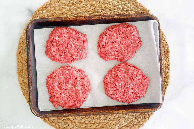 four ground beef patties on a tray.