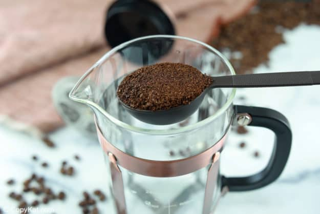 a scoop of coffee grounds over a French press.