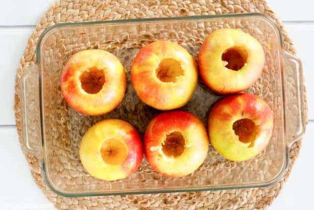 6 cored apples in a baking dish