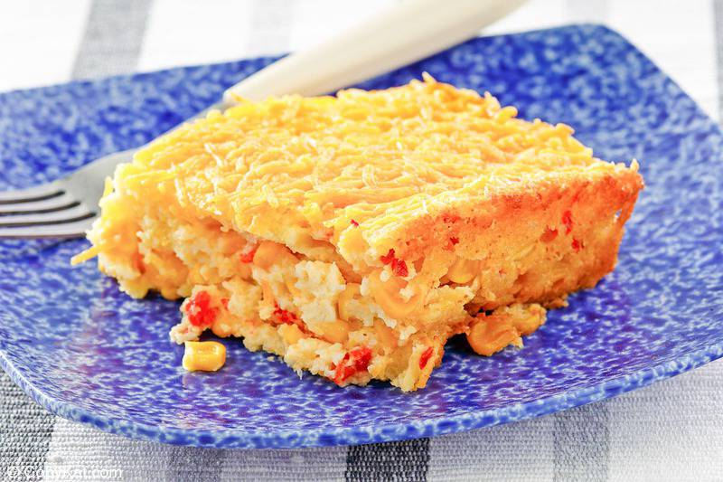 a serving of creamed corn casserole and a fork on a blue plate