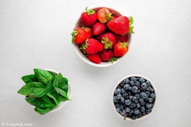 strawberries, blueberries, and fresh basil leaves.