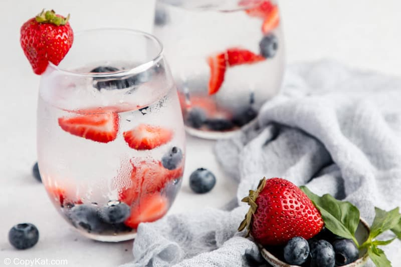 glasses filled with fruit infused water and fresh fruit.