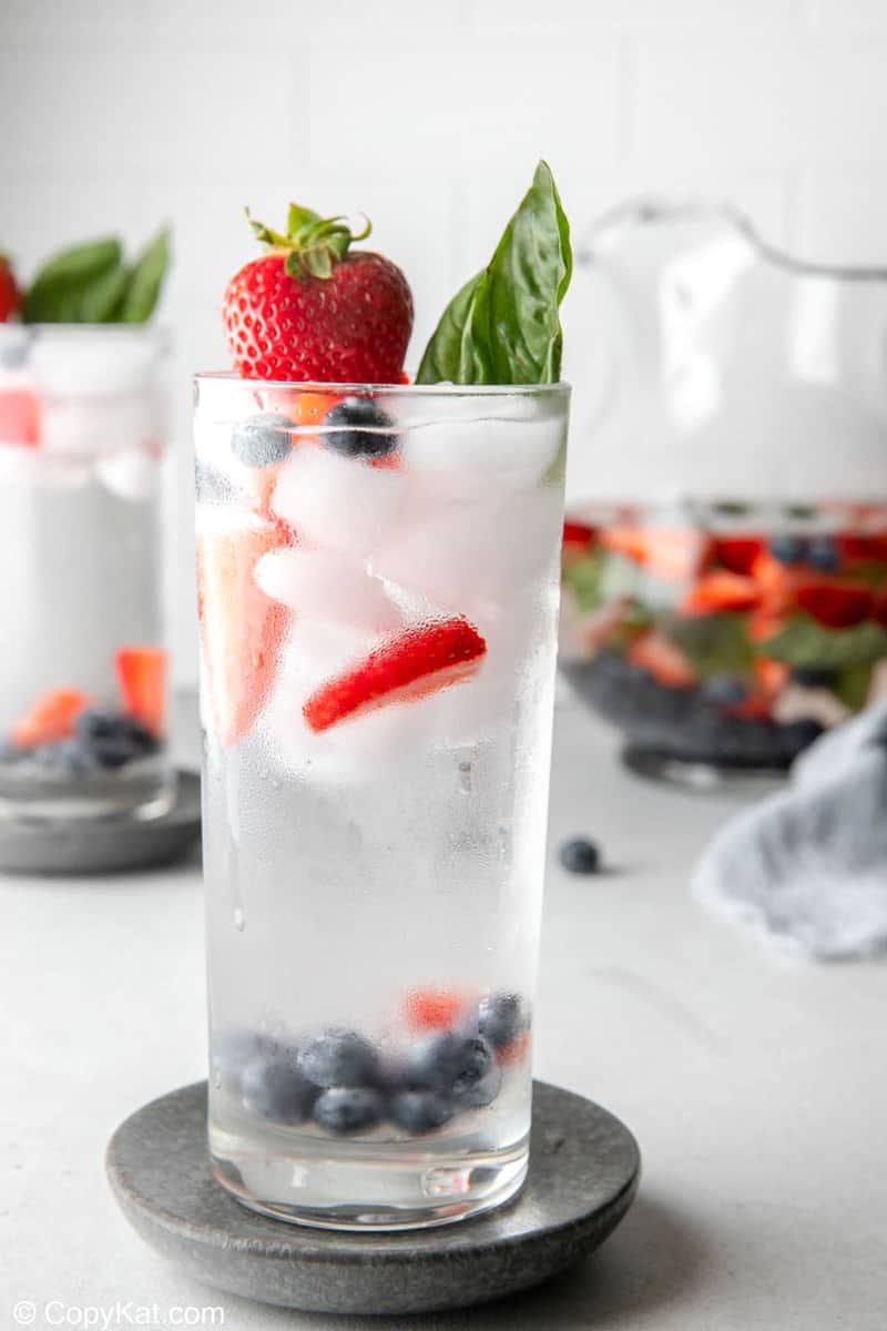tall glass filled with fruit infused water, fresh fruit, and ice.