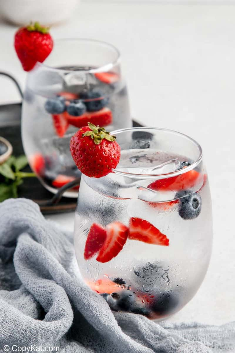 glasses of fruit infused water and fresh fruit.