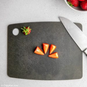 hulled and quartered strawberry and a knife on a cutting board.