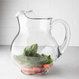 cut strawberries and basil in a pitcher.