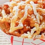 closeup of funnel cake fries in a paper serving dish