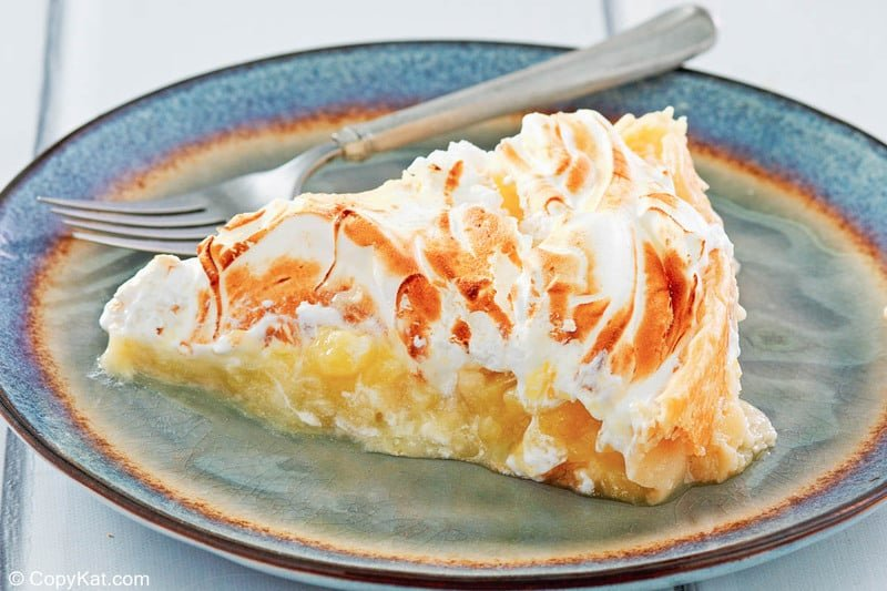 a slice of lemon meringue pie and a fork on a plate