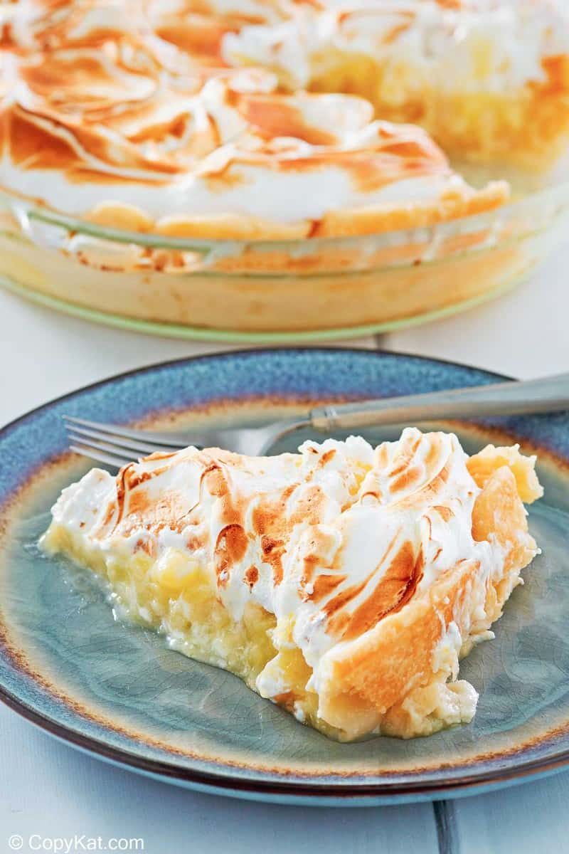 a slice of lemon meringue pie on a plate with the pie behind it