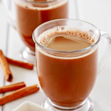 two mugs of Mexican coffee and cinnamon sticks