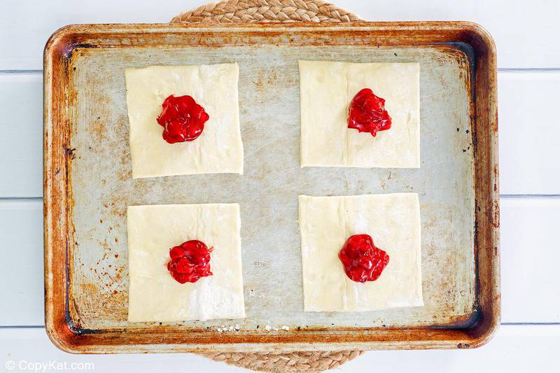 puff pastry square with cherry pie filling in the center of each one