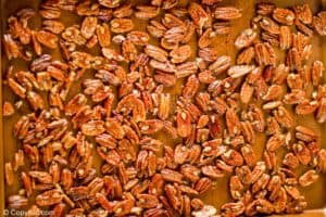 spiced pecans on a baking sheet before roasting
