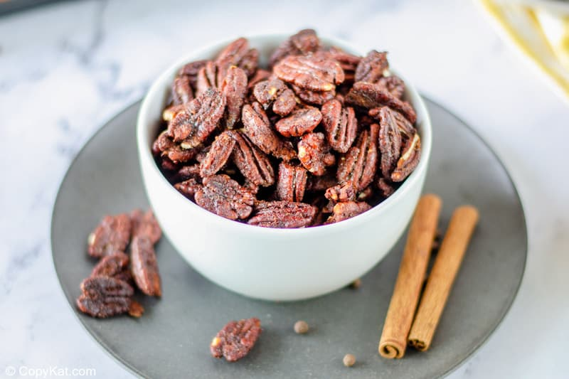 a bowl of spiced pecans and two cinnamon sticks on a plate