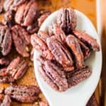 spiced pecans on a spoon and baking sheet