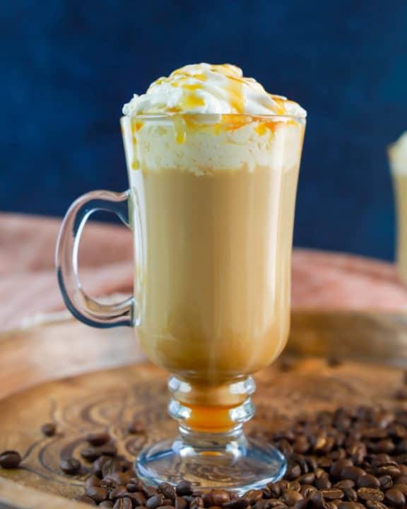 homemade Starbucks caramel macchiato on a wood tray.
