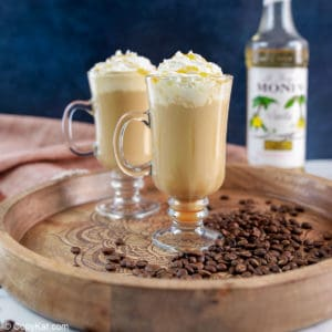 two caramel macchiato coffee drinks topped with whipped cream and caramel sauce