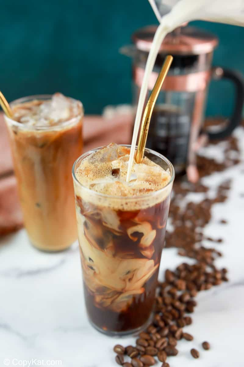 pouring vanilla sweet cream into a glass with cold brew coffee and ice.