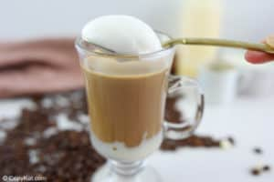 a spoonful of frothed milk foam over a white chocolate mocha.