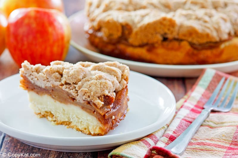 apple coffee cake with crumb topping slice on a plate.