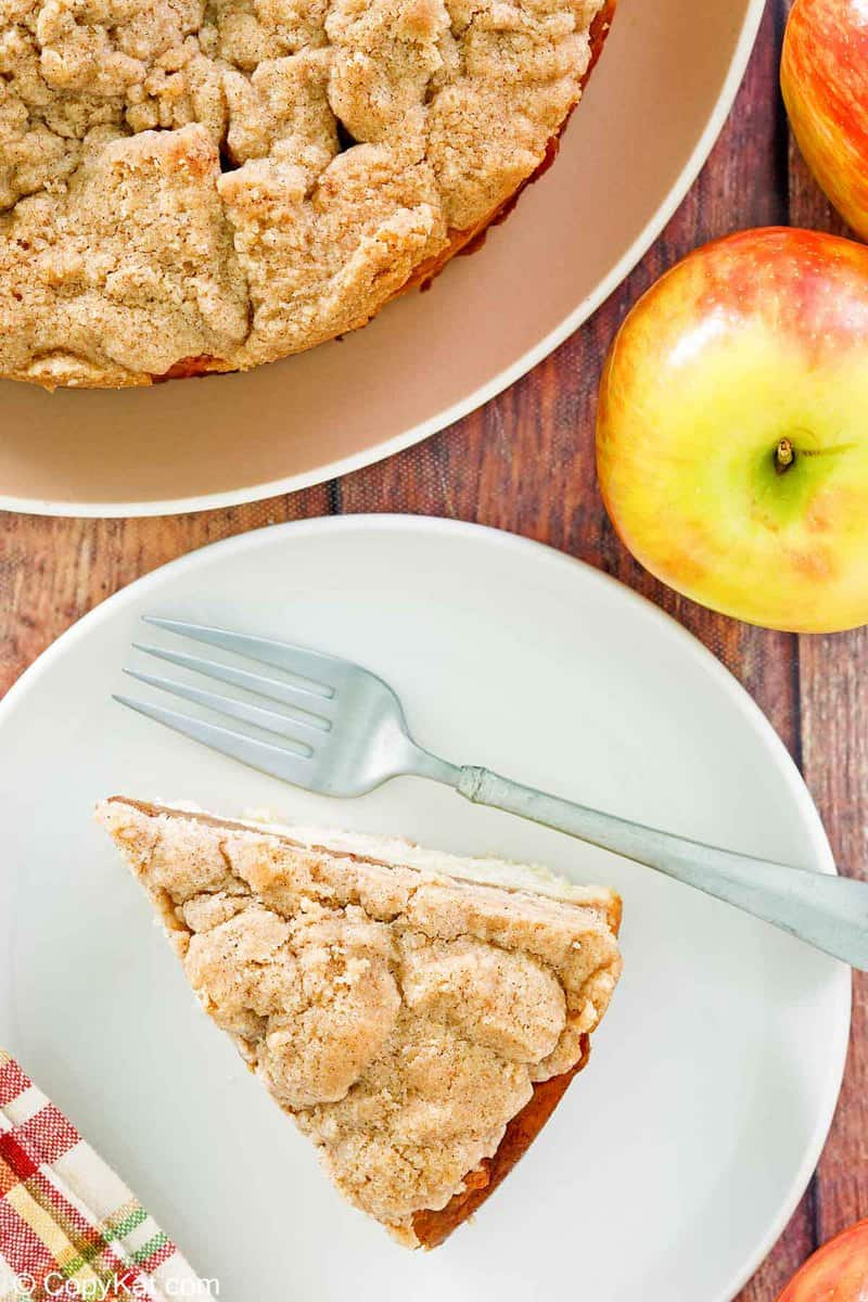 overhead view of apple coffee cake with crumb topping and apples.