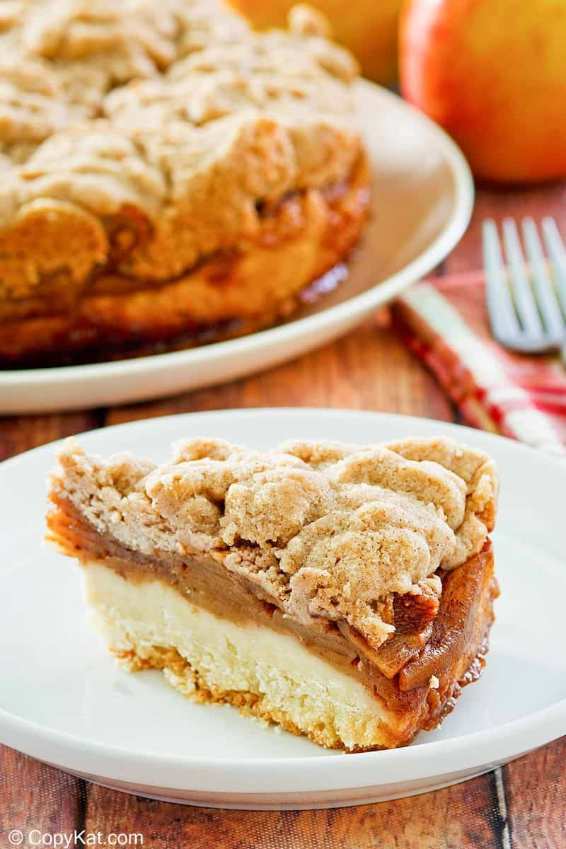 a slice of apple coffee cake with crumb topping on a plate.