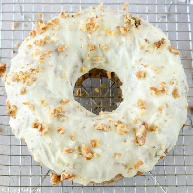 apple spice cake with cream cheese frosting topped with chopped walnuts.