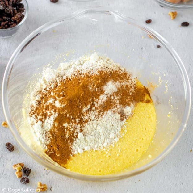 adding dry ingredients to wet ingredients for spice cake.
