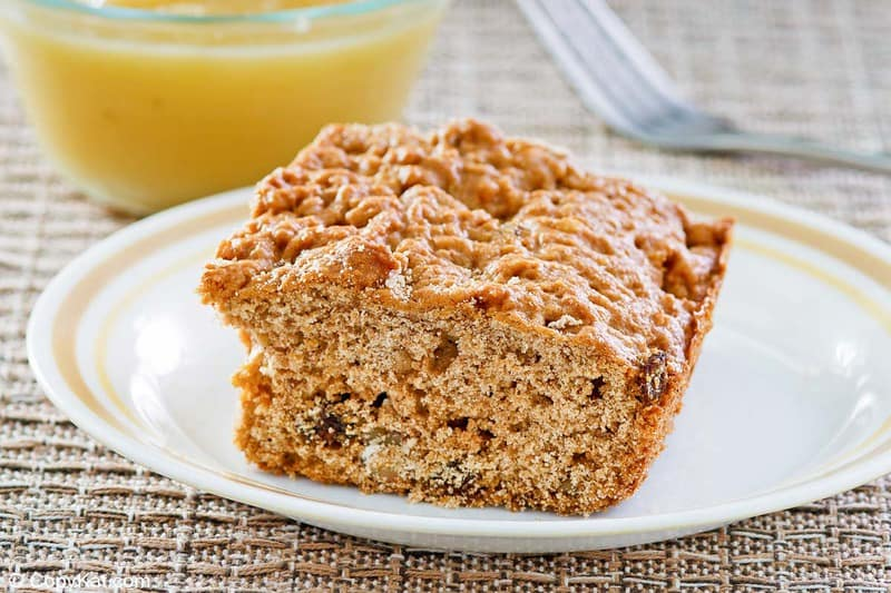 applesauce cake slice on a plate and a small bowl of applesauce.