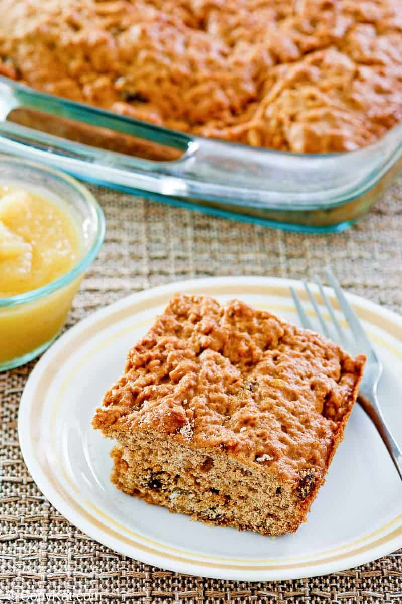 applesauce cake slice on a plate and the cake in a glass baking dish.
