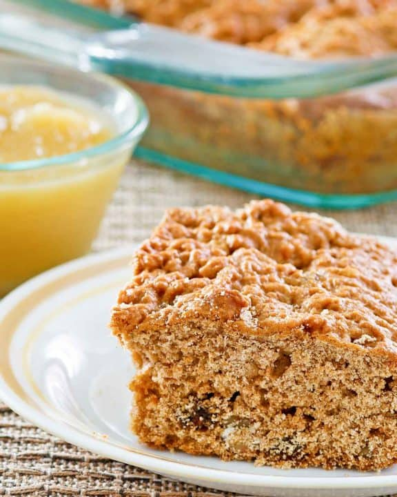 a slice of applesauce cake on a plate and applesauce in a small bowl.