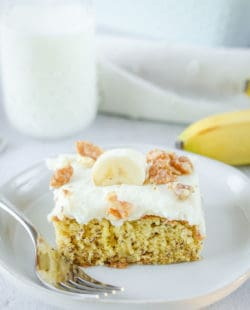 banana cake slice and a fork on a plate and a glass of milk.