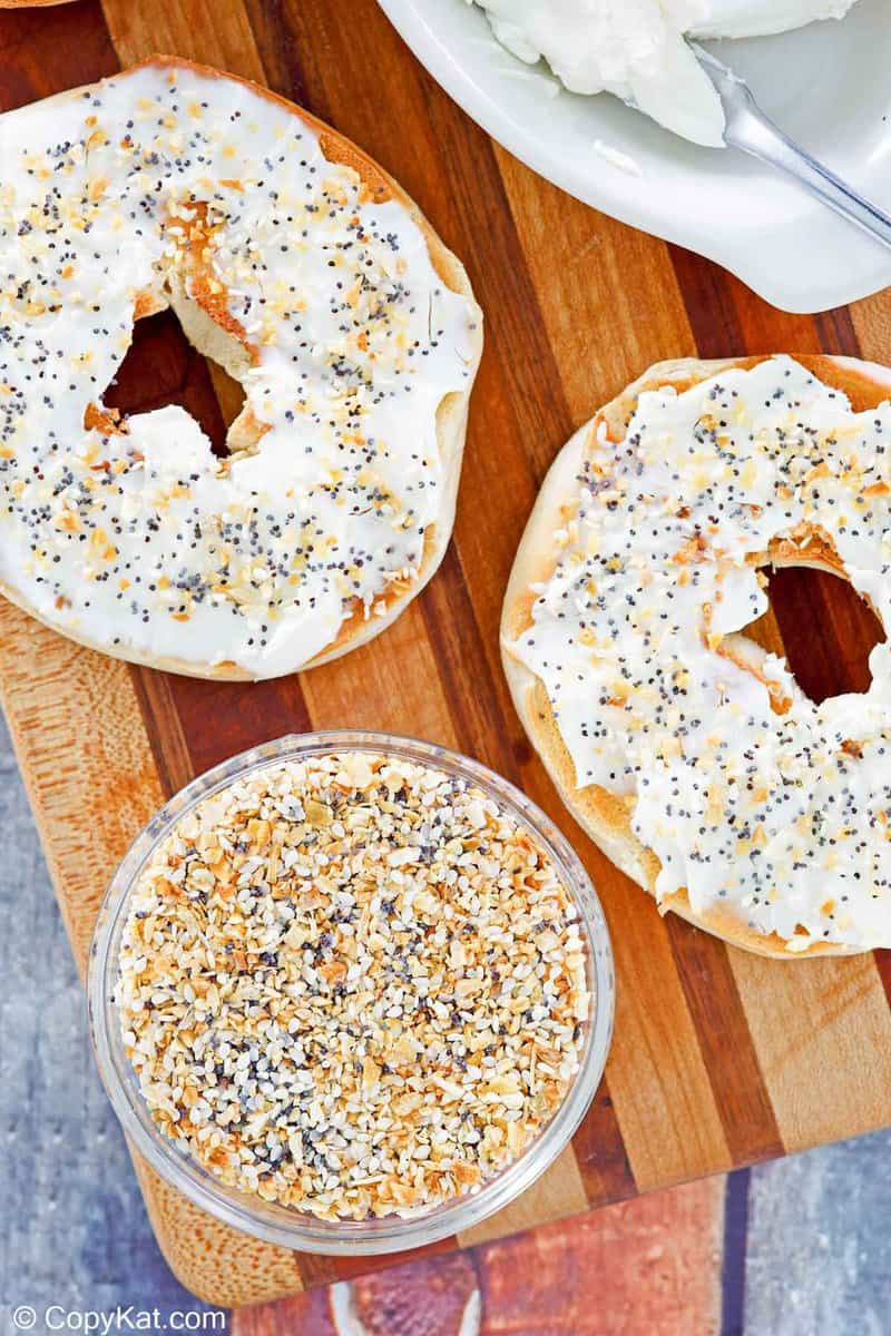 a bowl of homemade everything bagel seasoning and a bagel with cream cheese.