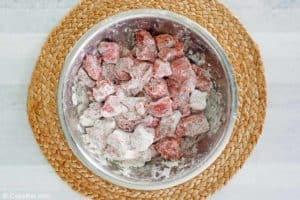 floured round steak pieces in a bowl.