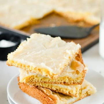 four gooey butter cake slices on a plate in front of the cake in a pan.