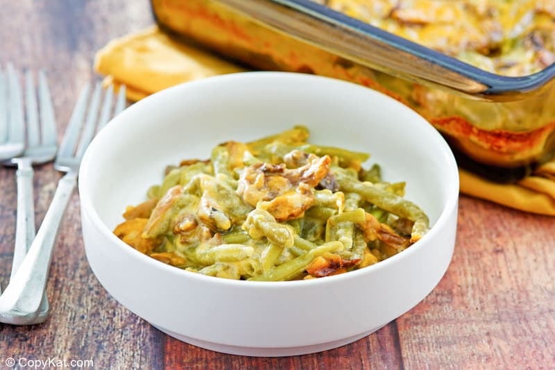 bowl of green bean casserole with cheese and two forks.