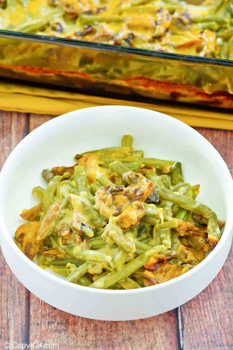 green bean casserole with cheese in a bowl in front of it in a baking dish.