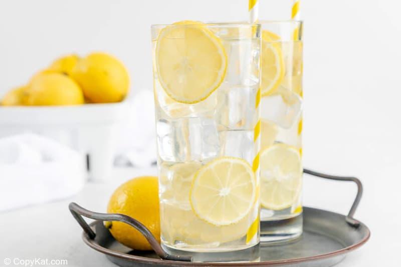 two glasses of homemade lemonade on a tray and a basket of lemons.