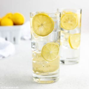 homemade lemonade, ice, and lemon slices in two glasses.