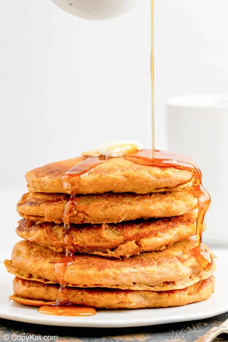 a stack of homemade IHOP pumpkin pancakes with syrup flowing over them.
