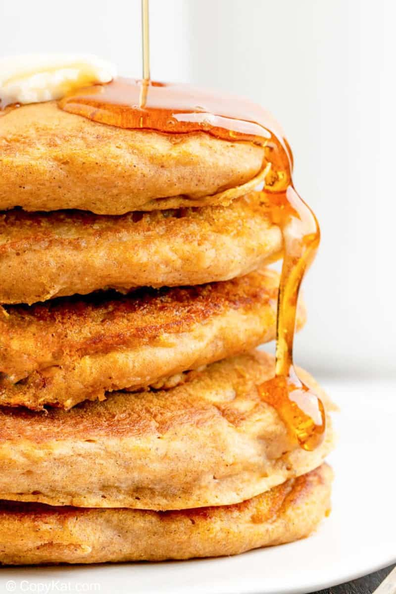 a stack of 5 homemade IHOP pumpkin pancakes with syrup running down the side.