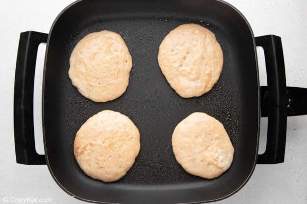 four portions of pumpkin pancake batter on a griddle.
