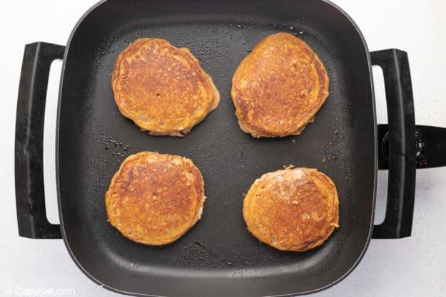 four pumpkin pancakes on a griddle.