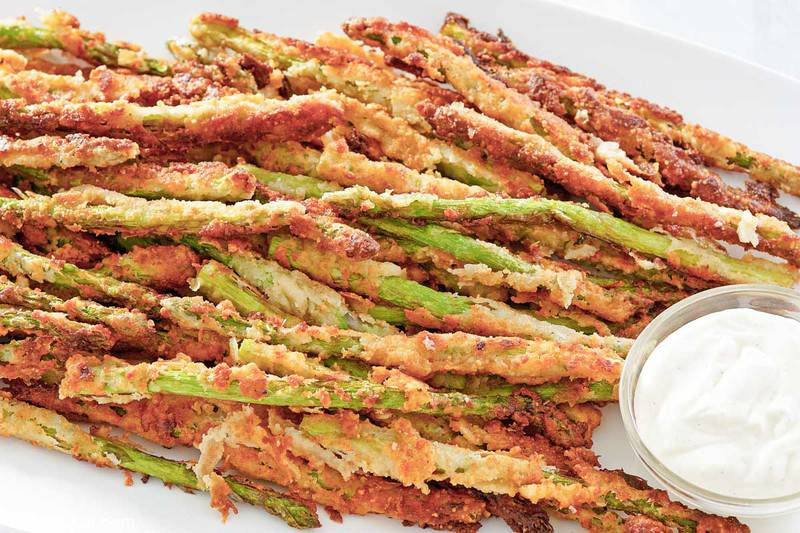homemade Longhorn Steakhouse parmesan crusted asparagus and a small bowl of ranch sauce.