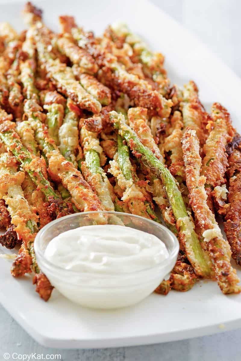 homemade Longhorn parmesan crusted asparagus and ranch sauce on a platter.