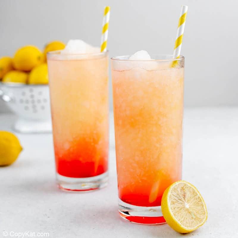 two homemade McDonald's frozen strawberry lemonade drinks and fresh lemons.