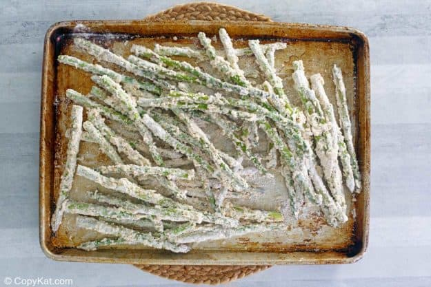 parmesan and flour coated asparagus on a baking sheet.
