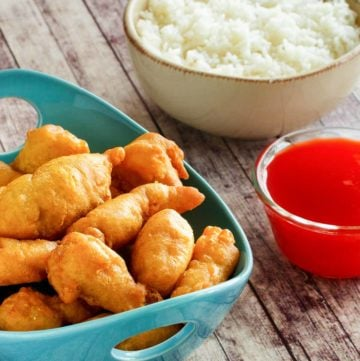 sweet and sour chicken, sauce, and a bowl of rice.