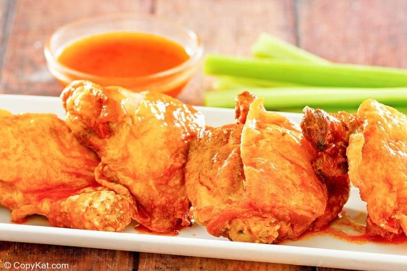 homemade Wingstop Buffalo chicken thighs, celery sticks, and Buffalo sauce.