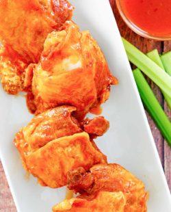 four homemade Wingstop Buffalo chicken thighs, Buffalo sauce, and celery sticks.